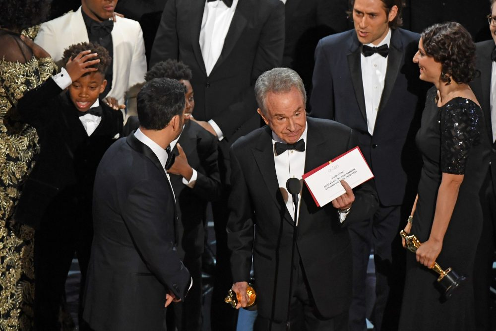 "The casts of ""Moonlight"" and ""La La Land"" appear on stage as presenter Warren Beatty (center) shows the winner's envelope for Best Picture. (Mark Ralston/AFP/Getty Images)"