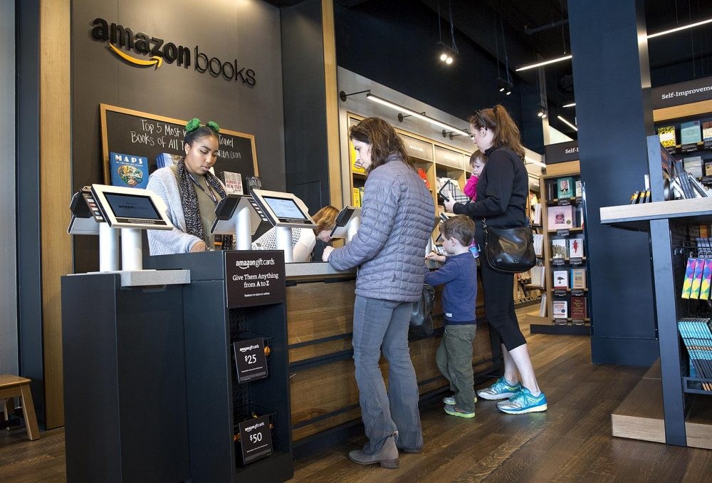 Jessica Booker, left, completes a book sale at the Amazon store in Dedham. (Robin Lubbock/WBUR)