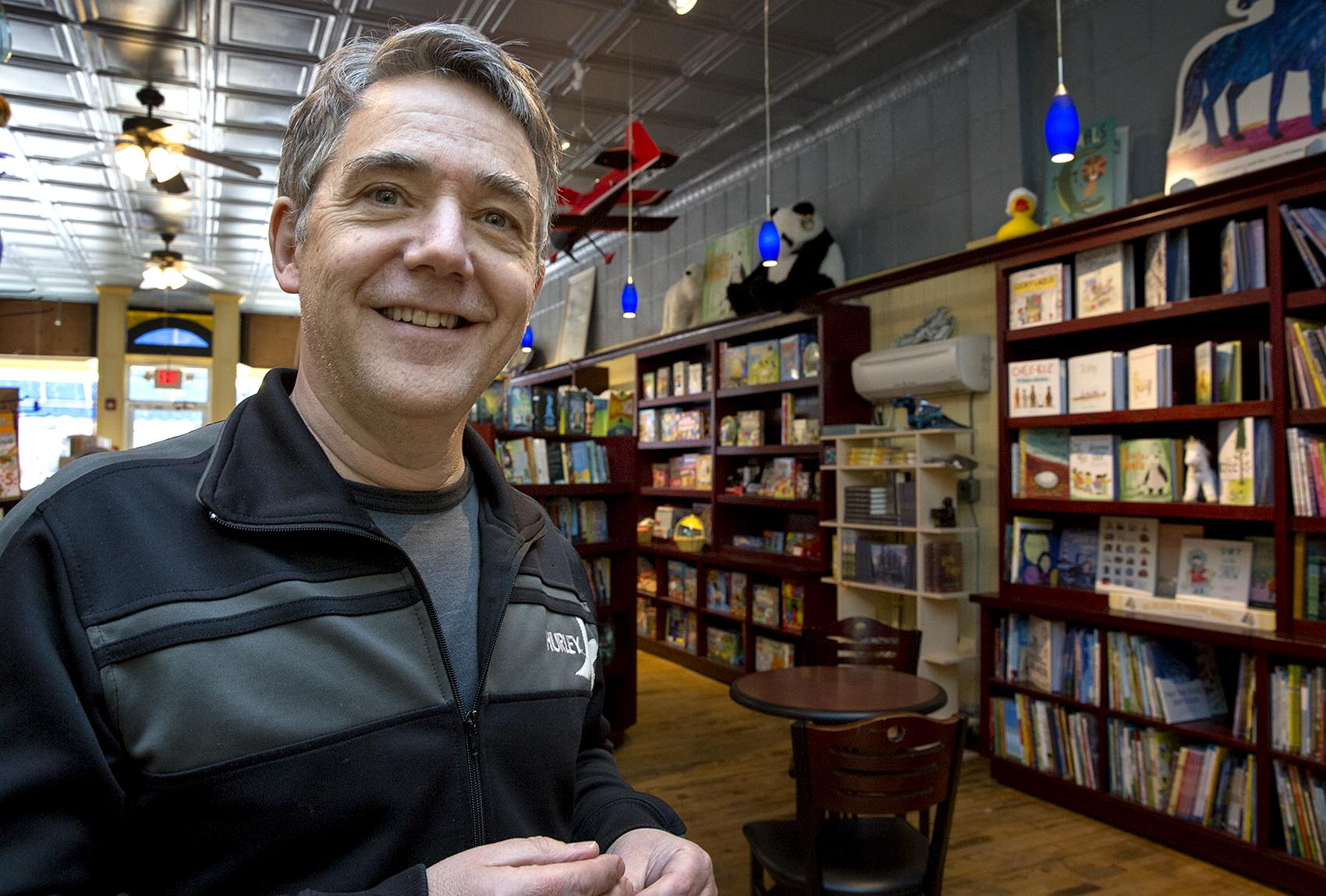 Peter H. Reynolds, owner of The Blue Bunny Bookstore in Dedham stands surrounded by books on the day Amazon also opened a bookstore in the town. He said independent bookstores are an endangered species and need to be supported so they can stick around. (Robin Lubbock/WBUR)