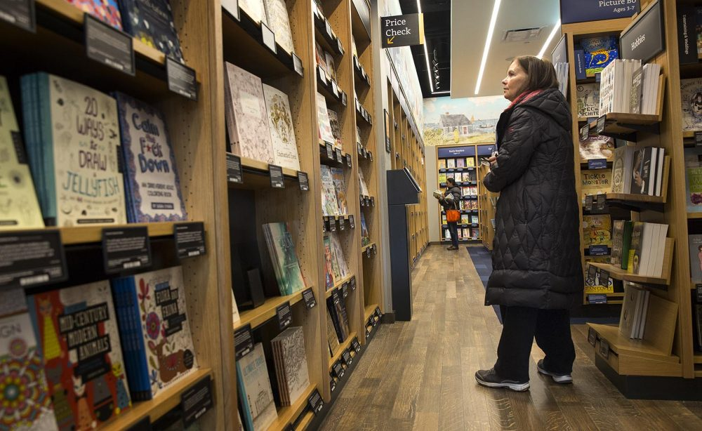 "Susan Crowley, of Westwood, browsed for books at the new Amazon bookstore in Dedham. ""I love books and just having Amazon here sounded so great,"" she said. ""So I wanted to see what it's all about. And I love having it so close to home."" (Robin Lubbock/WBUR)"