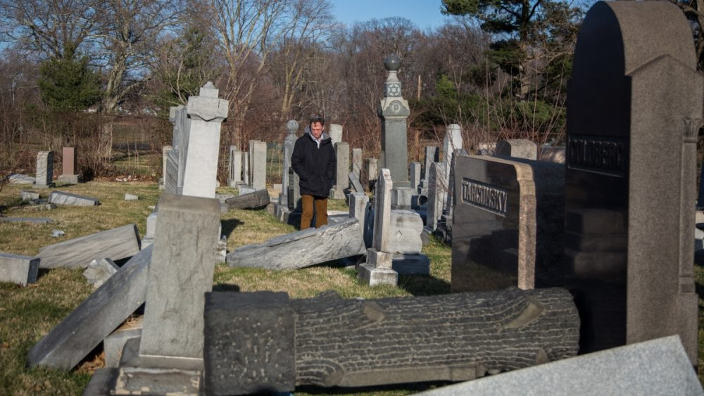 Rabbi Adam Zeff from the Germantown Jewish Centre surveys the damage at the Mt Carmel Cemetery (Emily Cohen for NewsWorks)