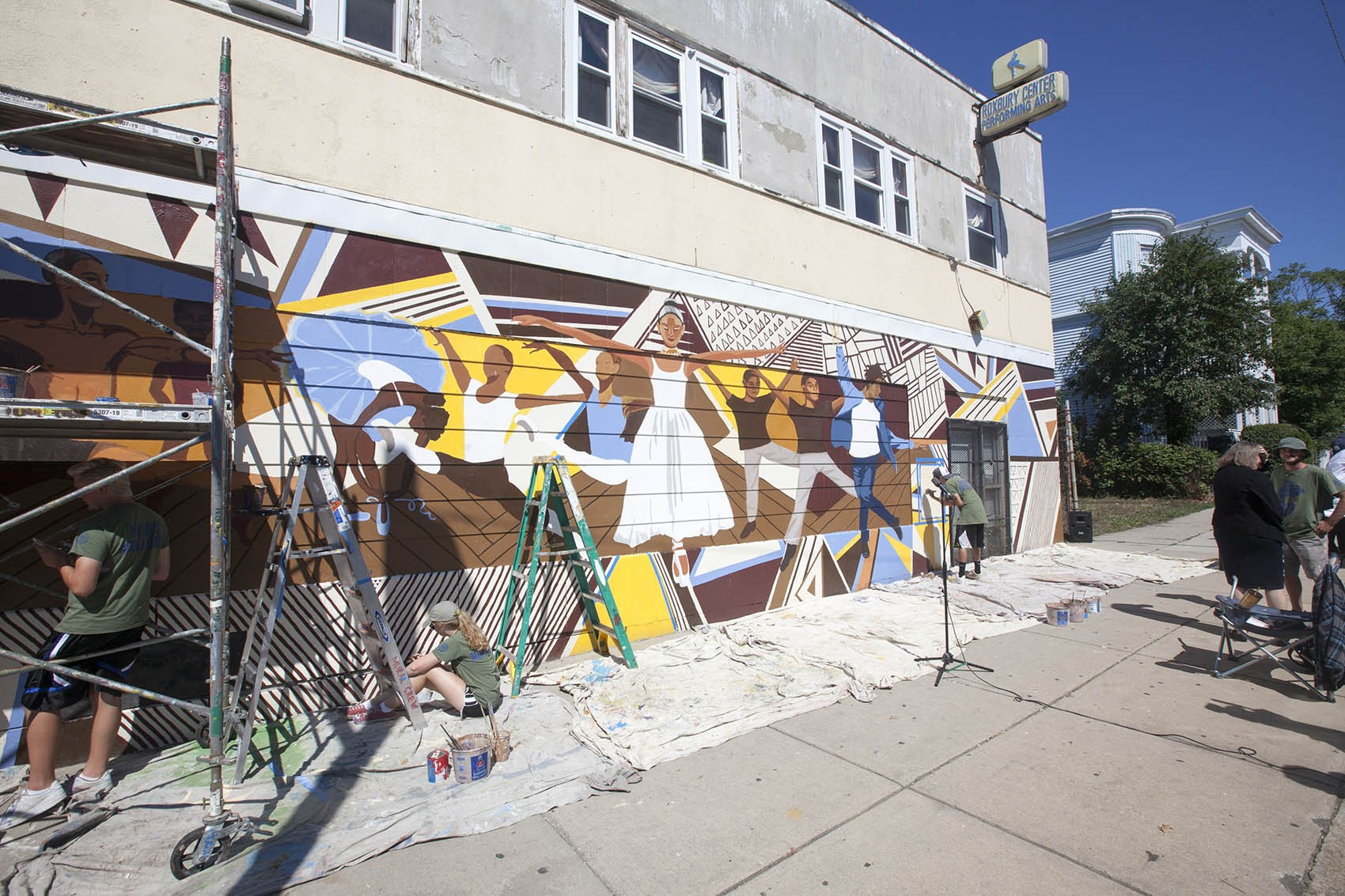 The mayor's mural crew paints the Roxbury Center for Performing Arts last summer. (Joe Difazio for WBUR.)