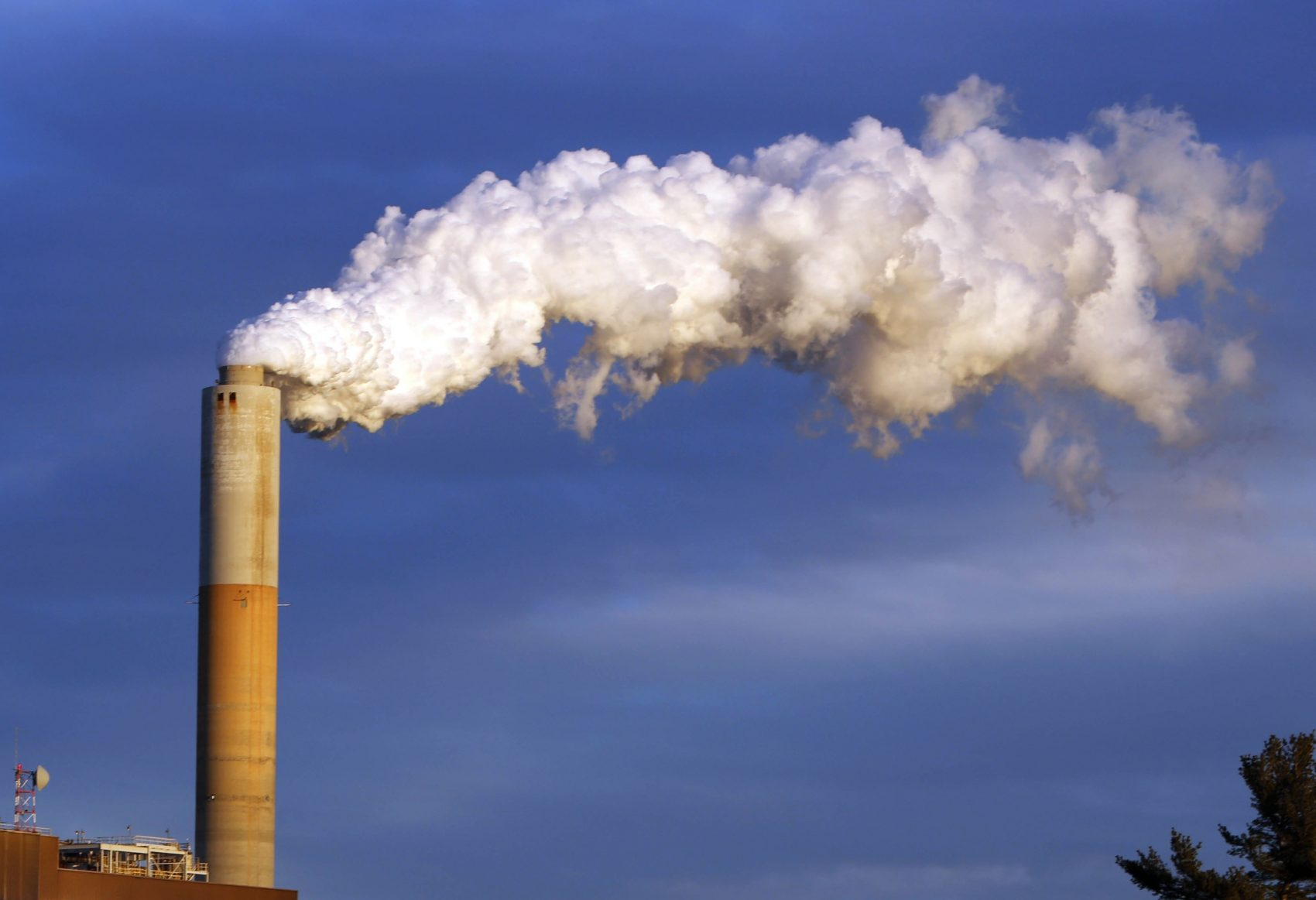 Economists overwhelmingly would vote to tax the carbon content of fuels to curtail climate change. Could the carbon tax win over the climate-change-denying troglodytes in the GOP? Pictured: In this Jan. 20, 2015 file photo, steam billows from the chimney of a coal-fired Merrimack Station in Bow, N.H. (Jim Cole/AP)