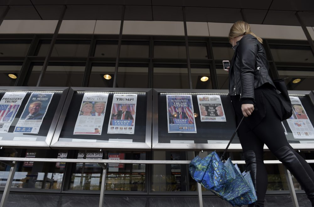 A woman views the front pages of newspapers on display outside the Newseum in Washington on Nov., 9, 2016, the day after the presidential election. (Susan Walsh/AP)