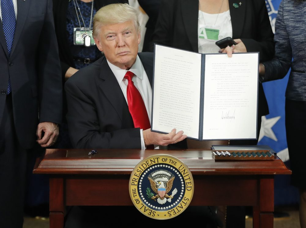President Trump holds up an executive order for border security and immigration enforcement improvements during a visit to the Homeland Security Department headquarters in Washington on Jan. 25. (Pablo Martinez Monsivais/AP)