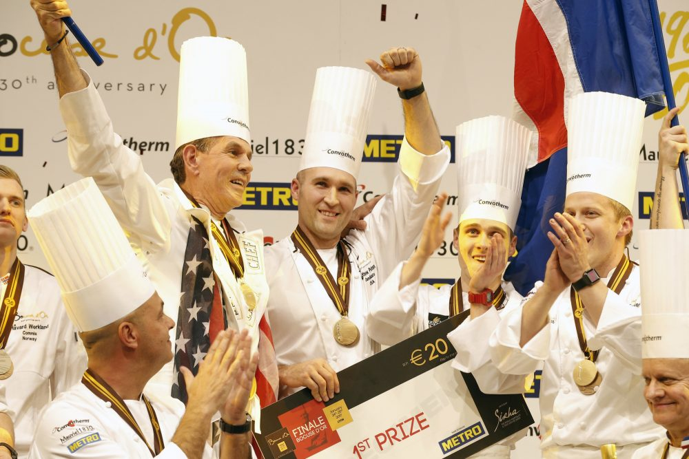 "With so many chefs not represented by Team USA, writes Joshua Lewin, I am left wondering what message we are sending the world about the true richness of America's culinary landscape. Pictured: Mathew Peters of USA, centre, celebrates on the podium with teammates after winning the ""Bocuse d'Or"" (Golden Bocuse) trophy, in Lyon, central France, Wednesday, Jan. 25, 2017. The contest, a sort of world cup of the cuisine, was started in 1987 by Lyon chef Paul Bocuse to reward young international culinary talents. (Laurent Cipriani/AP)"