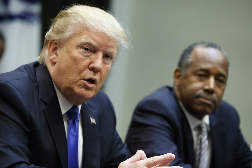 The rising murder rate in Chicago is a serious problem, writes Kevin C. Peterson. But Trump has turned the violence into an unfair stereotype of African Americans. Pictured: Housing and Urban Development Secretary-designate Ben Carson listens at right as President Donald Trump speaks during a meeting on African American History Month in the Roosevelt Room of the White House in Washington, Wednesday, Feb. 1, 2017. (Evan Vucci/AP)