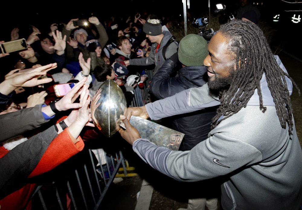 Patriots running back LeGarrette Blount holds the Super Bowl trophy for fans following the team's arrival at Gillette Stadium Monday night. (Steven Senne/AP)