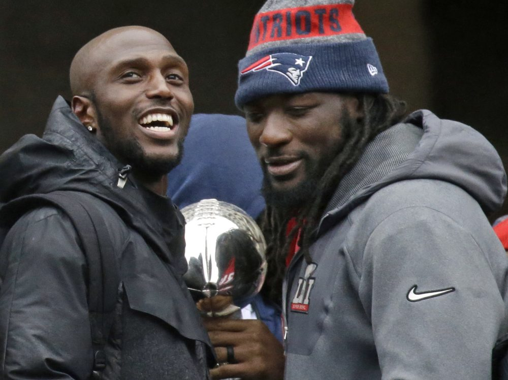 Patriots safety Devin McCourty, left, and running back LeGarrette Blount, seen here during the team's parade through Boston Tuesday, have both announced they're skipping the traditional White House visit for Super Bowl champions. (Elise Amendola/AP)
