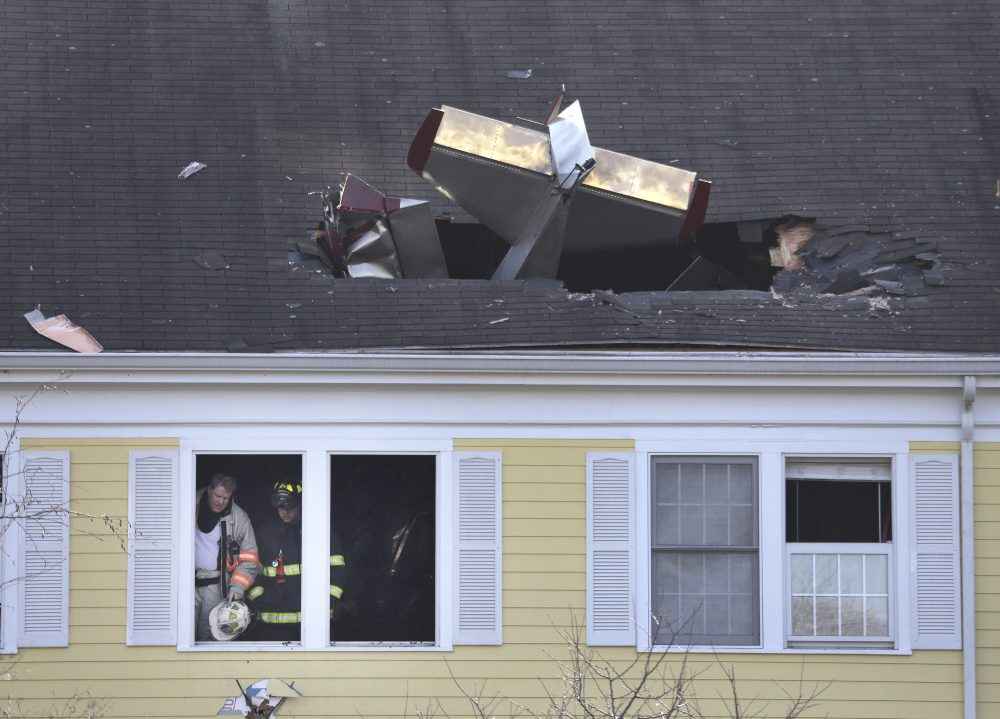 Firefighters investigate the scene after a small plane crashed into the roof of a condominium building in Methuen, Tuesday. (Elise Amendola/AP)