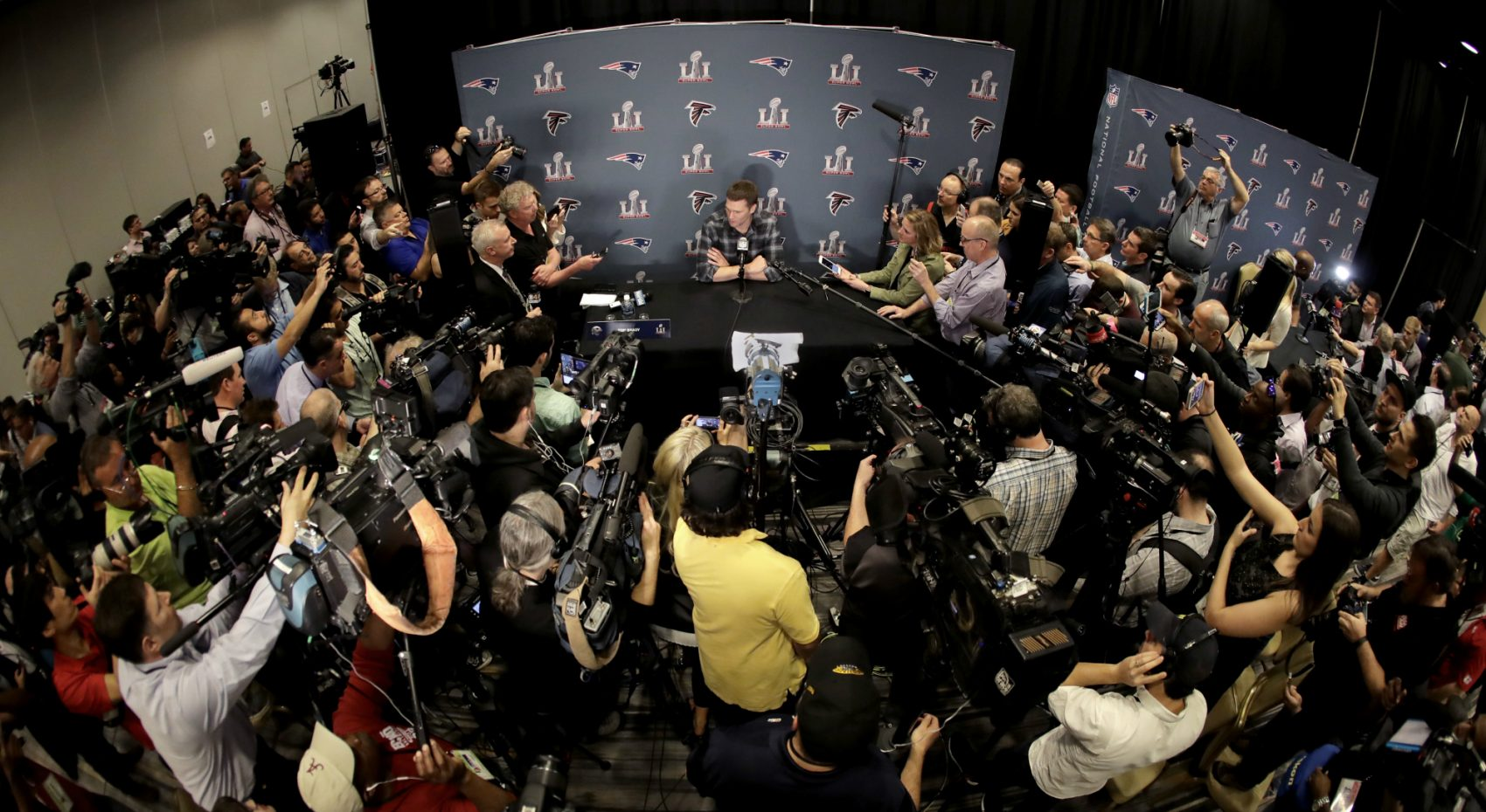 Pre-Super Bowl Houston feels like an alternate reality, writes Shira Springer. It's a land in which Tom Brady's brand of blinders-on positivity can thrive, and the NFL brand can shine. Pictured: New England Patriots quarterback Tom Brady talks to the media during a news conference for the NFL Super Bowl 51 football game against the Atlanta Falcons. Tuesday, Jan. 31, 2017, in Houston. (Charlie Riedel/AP)