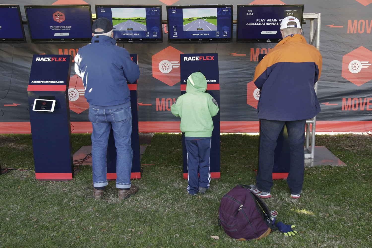 In this file photo, adults as well as kids enjoy a racing video game at the NASCAR Acceleration Nation interactive display at Daytona International Speedway. (John Raoux/AP)