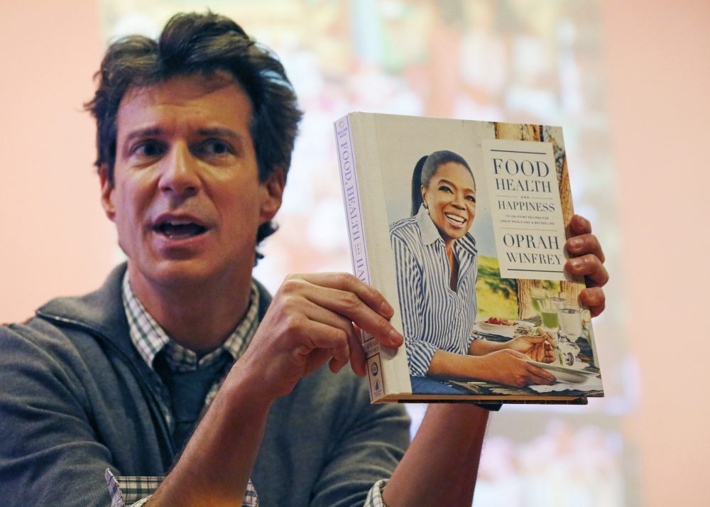 "O Magazine creative director Adam Glassman displays a copy of Oprah Winfrey's ""Food Health and Happiness."" (Kathy Willens/AP)"