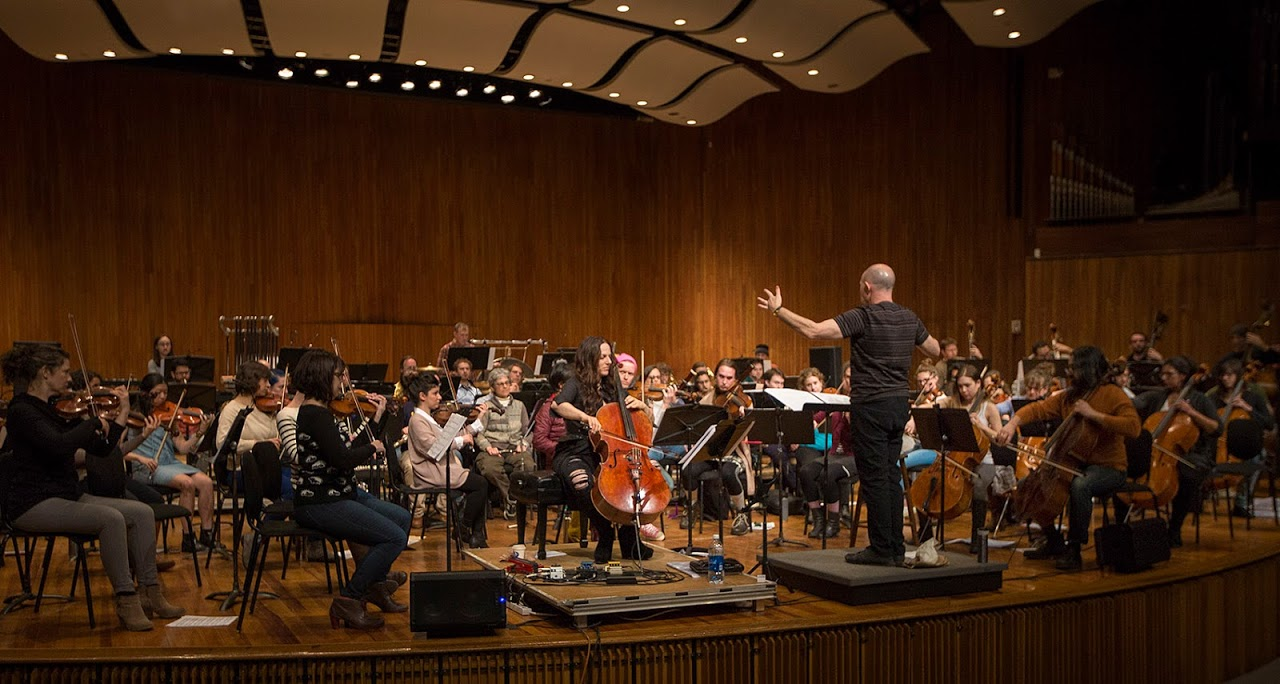 """MIT professor Evan Ziporyn conducts a rehearsal of his arrangement of David Bowie's """"Blackstar"""" featuring cellist Maya Beiser. (Jesse Costa/WBUR)"""