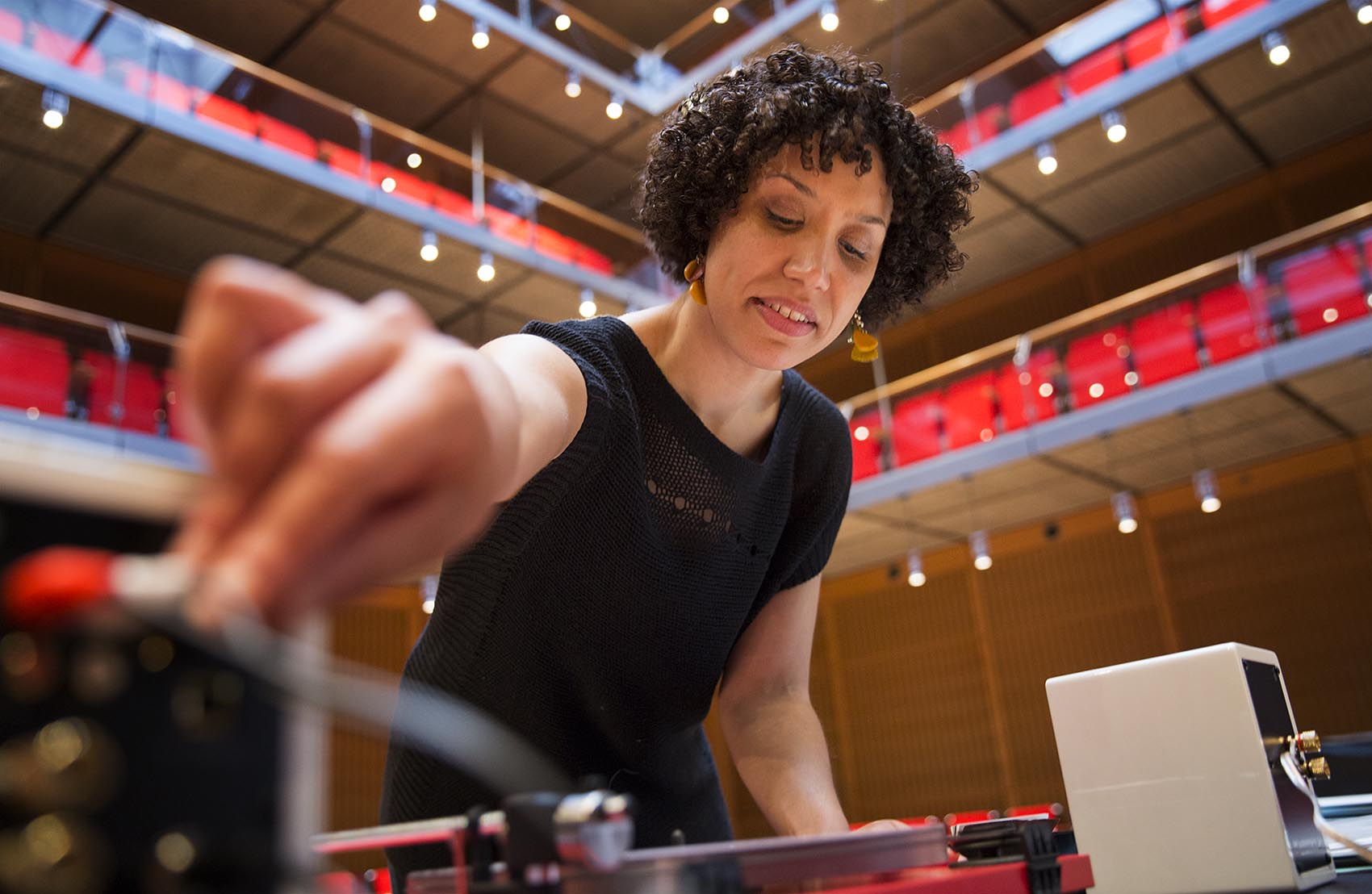 """Artist Elisa Hamilton adjusts the volume of the """"Sound Lab"""" turntable. (Robin Lubbock/WBUR)"""