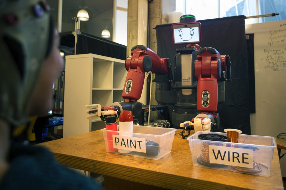 Researchers at MIT have created a system where humans can guide robots through simple binary activities with their brainwaves. Here, robot Baxter sorts items while a person observes. If the human notices a mistake, their brainwaves will automatically signal to the system that something has gone wrong and Baxter will attempt to correct himself. (Jesse Costa/WBUR)