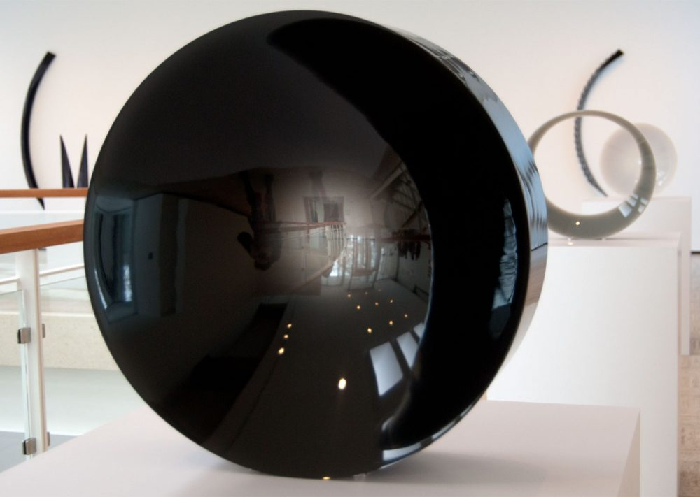 "Fred Eversley's untitled 1974 cast polyester resin lens (center) in the exhibit ""Black, White, Gray,"" an exhibition at Brandeis University's Rose Art Museum. (Greg Cook/WBUR)"