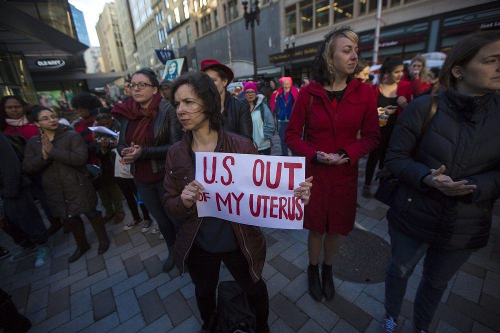 "Noelle Cocoros, a research scientist at Harvard Medical School, held a sign that read, ""U.S. out of my uterus"" during the ""A Day Without Women"" rally at Downtown Crossing. (Jesse Costa/WBUR)"