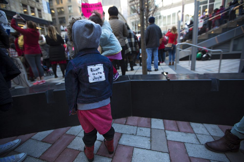"Three-year-old Ella Berg Power of Worcester wore a ""Power To The People"" patch on her back. (Jesse Costa/WBUR)"