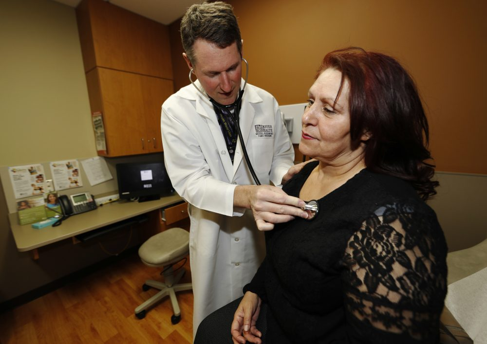 In this Thursday, March 9, 2017, photo, Dr. Michael Russum, left, checks patient Ruby Giron in Denver Health Medical Center's primary care clinic located in a low-income neighborhood in southwest Denver. (David Zalubowski/AP)