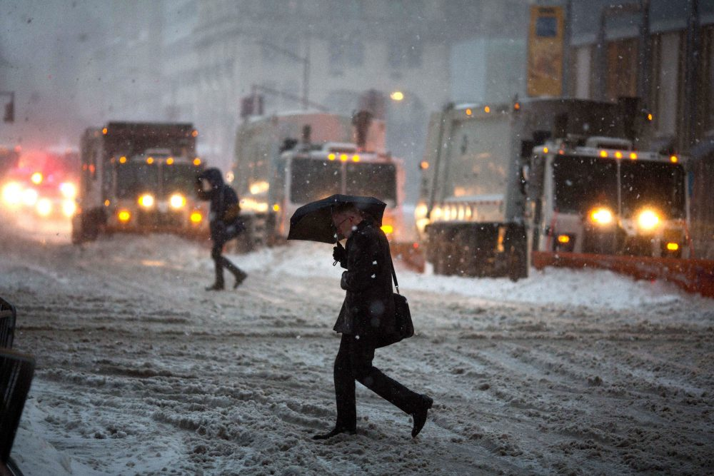 Snow plows line up on Fifth Avenue during a day of heavy snow and freezing rain on March 14, 2017, in New York. (Kevin Hagen/Getty Images)