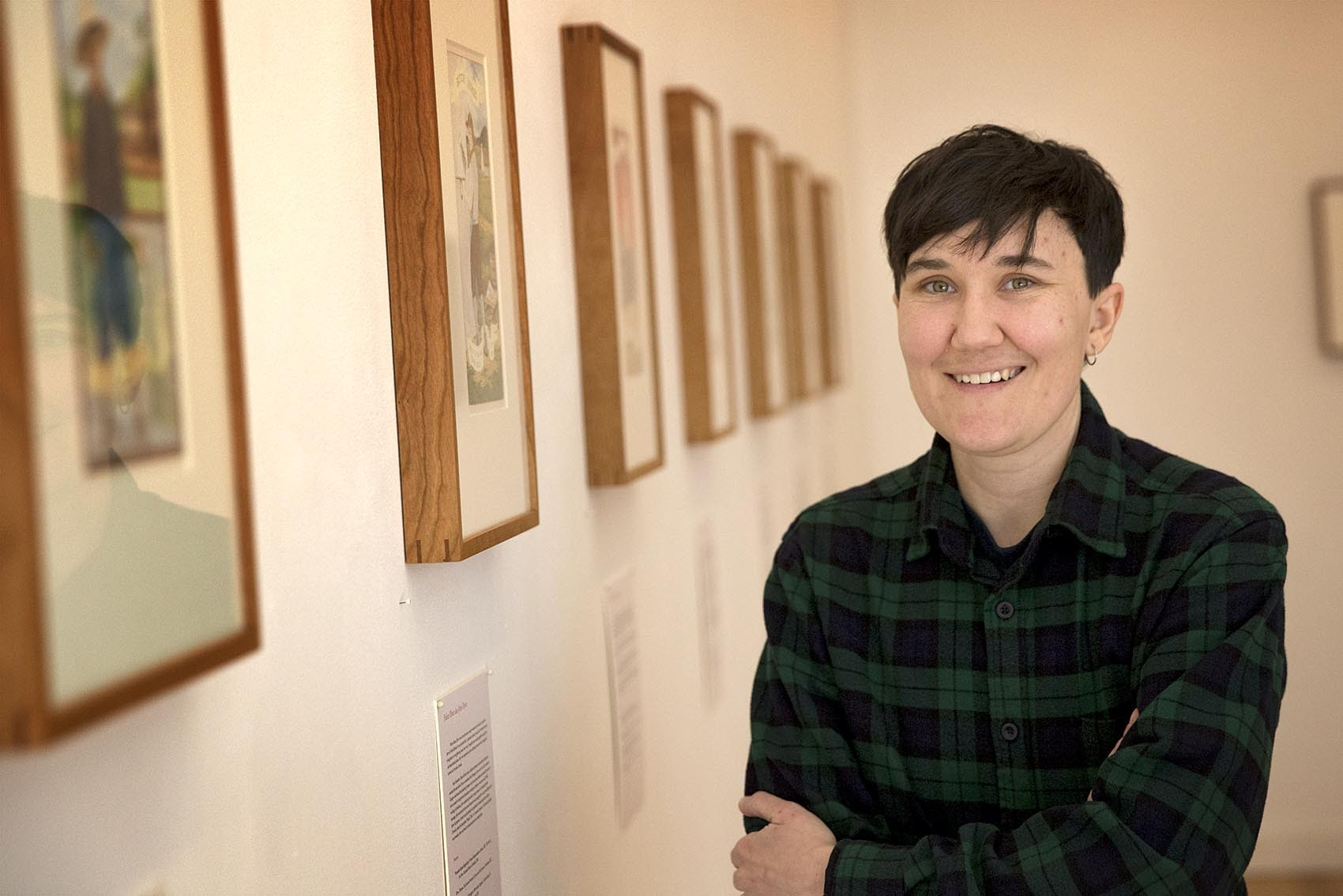Artist Ria Brodell stands next to paintings hanging at the Gallery Kayafas in Boston. (Robin Lubbock/WBUR)