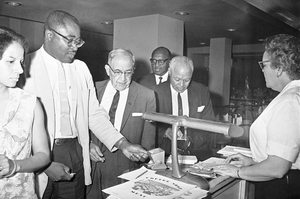 While Kenneth Guscott, president of the Boston NAACP chapter, reaches for a toothpick, Rev. R.L.T. Smith of Jackson reaches into wallet to pay coffee shop bill for the group of blacks, admitted for first time at a downtown Jackson, Miss., hotel in 1964. (Jim Bourdier/AP)