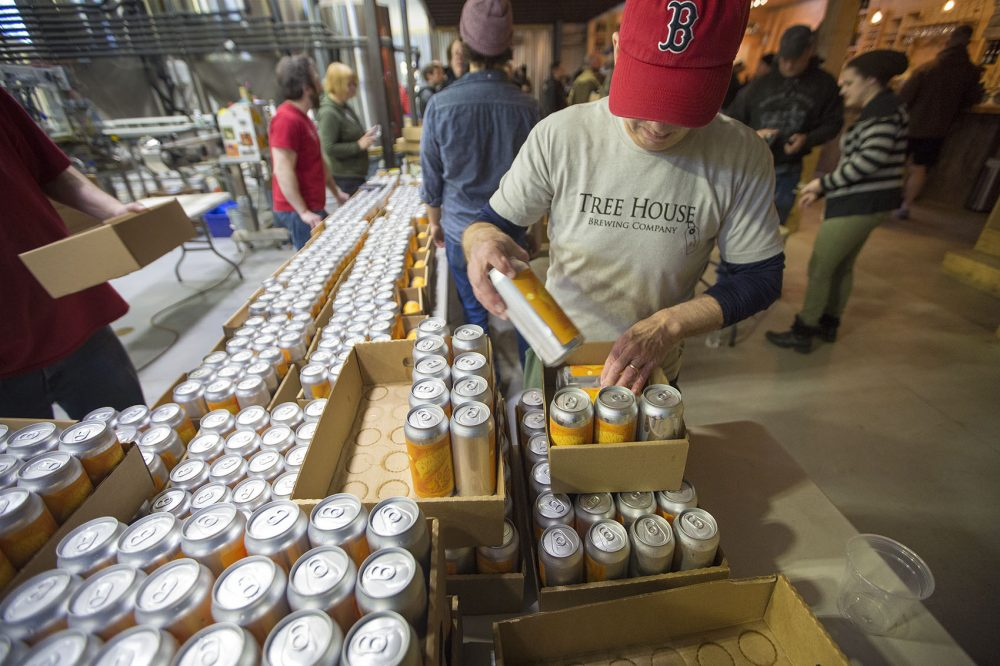A worker at Tree House Brewing Co. in Monson assembles 10 packs for sale. Tree House customers can wait in line for hours to purchase the company's craft brews. (Jesse Costa/WBUR)