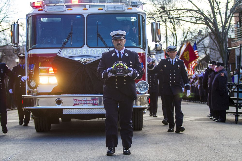 Lt. John Baccari carries the helmet of fallen Watertown firefighter Joseph Toscano as the funeral procession arrives at St. Patrick's Church Wednesday. Toscano collapsed while fighting a house fire on Friday. (Jesse Costa/WBUR)