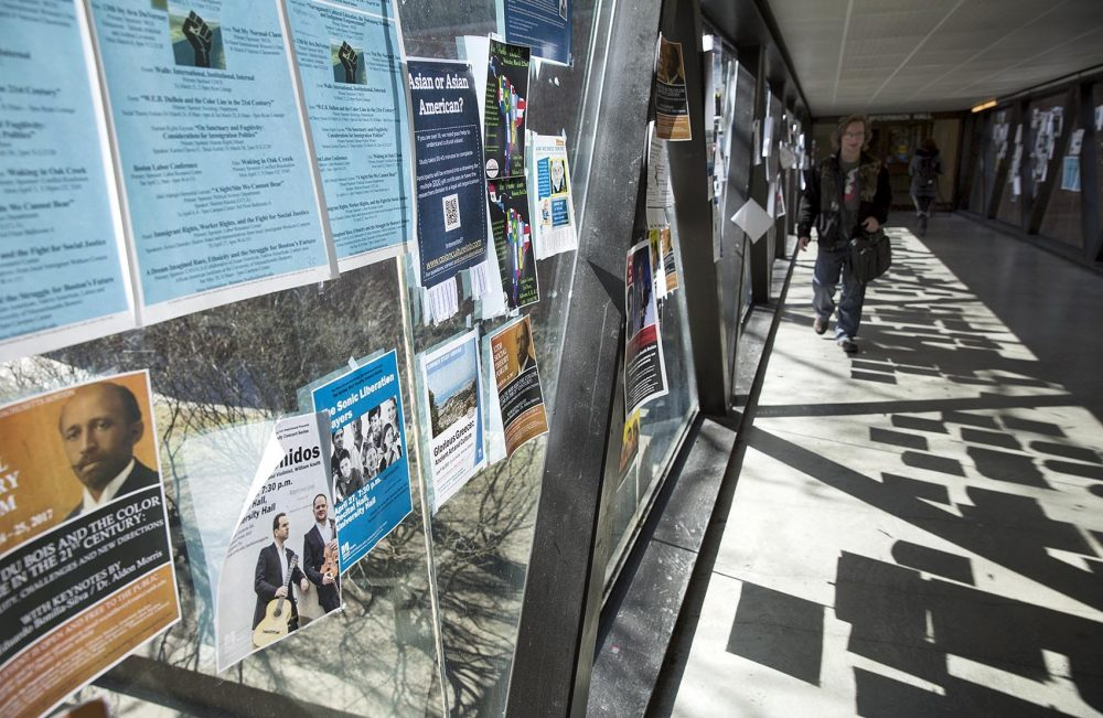 Event notices cover a glass wall in one of the elevated corridors on the UMass Boston campus. (Robin Lubbock/WBUR)
