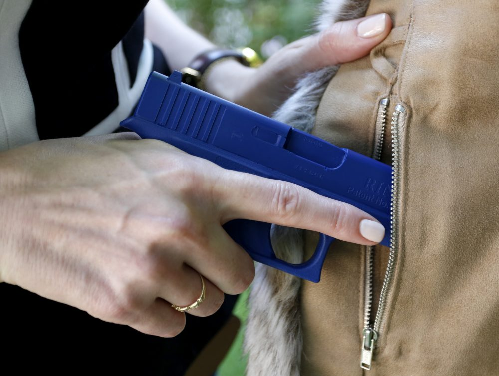 In this Aug. 29, 2016 photo, Marilyn Smolenski uses a mock gun to demonstrate how to pull a handgun out of the concealed carry clothing she designs at her home in Park Ridge, Ill. (Tae-Gyun Kim/AP)