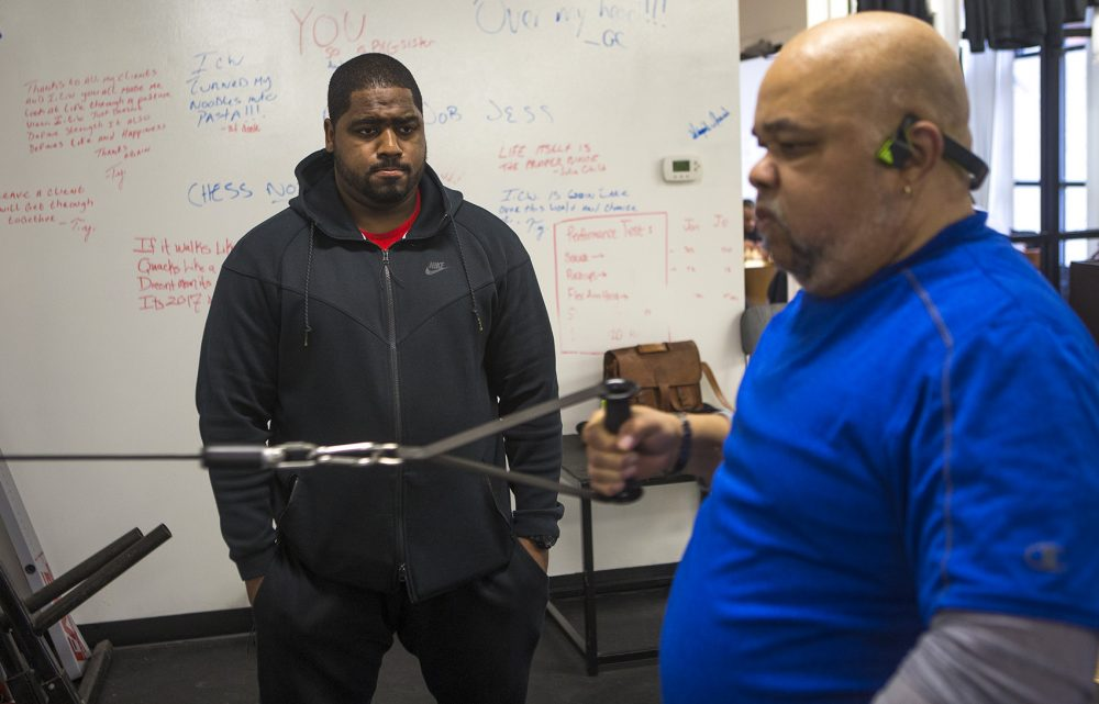 InnerCity Weightlifting trainer Angel LaCourt works with 65-year-old Cambridge resident Bill Gramby, who recently had a stroke and is working out to build strength and stamina. (Jesse Costa/WBUR)