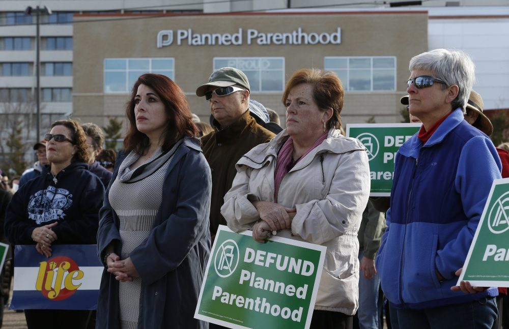 Participants in an anti-abortion rally hold signs and listen to a speaker in front of Planned Parenthood of the Rocky Mountains in Denver in February. (Brennan Linsley/AP)