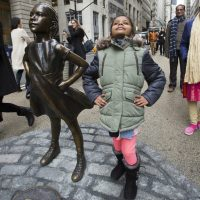 "Twice as many girls were taught to be nice and respectful, writes Deborah Pine, as those taught to be leaders. Pictured: Shriya Gupta of Cherokee, N.C. strikes a pose with a statue titled ""Fearless Girl,"" Wednesday, March 8, 2017, in New York. The statue was installed by an investment firm in honor of International Women's Day. (Mark Lennihan/AP)"