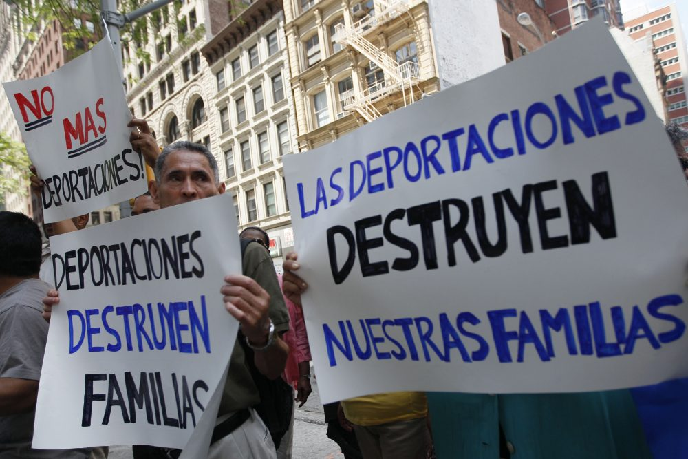 In this July 15, 2011 photo, demonstrators hold signs in New York during a rally to condemn an immigration and customs enforcement program known as Secure Communities. (Mary Altaffer/AP)