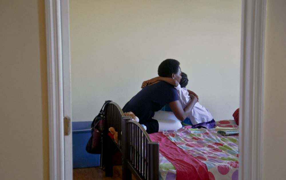 Tonia Handy, left, hugs her youngest child in their Brooklyn shelter in July 2016. (Bebeto Matthews/AP)