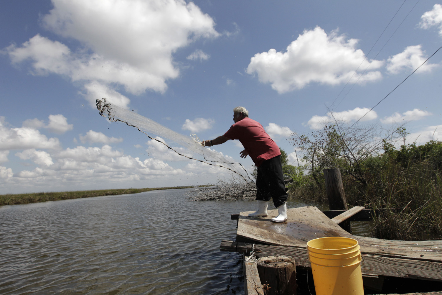 In this file photo, Edison Dardar, an American Indian, tosses a cast net for shrimp on the edge of Pointe- aux-Chenes wildlife management area, in Isle de Jean Charles, La. (Gerald Herbert/AP)
