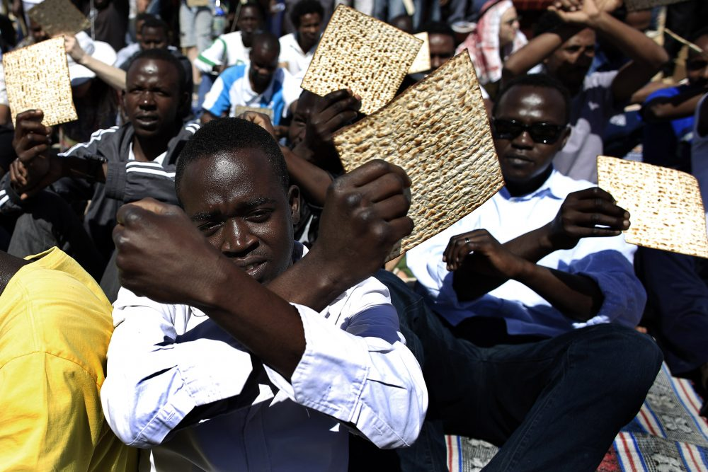 African migrants hold matzo, unleavened bread traditionally eaten by Jews during the week-long Passover holiday, as they protest outside the Holot detention center, southern Israel, in April 2014. (Tsafrir Abayov/AP)