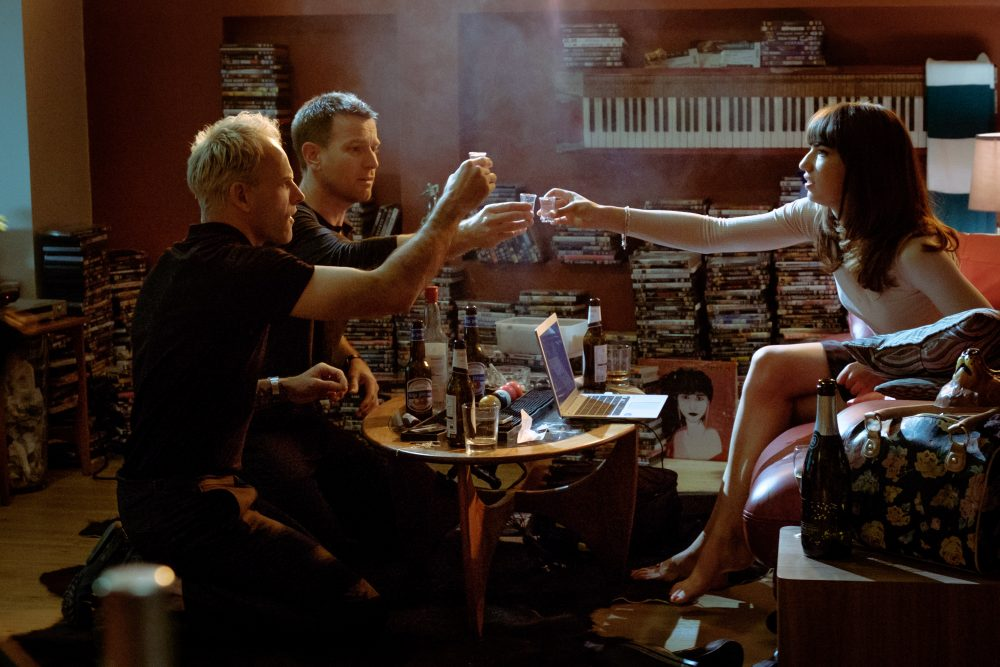 "Simon (Jonny Lee Miller), Mark (Ewan McGregor) and Veronika (Anjela Nedyalkova) drinking in Simon's flat in ""T2 Trainspotting."" (Courtesy Jaap Buitendijk/CTMG Inc.)"