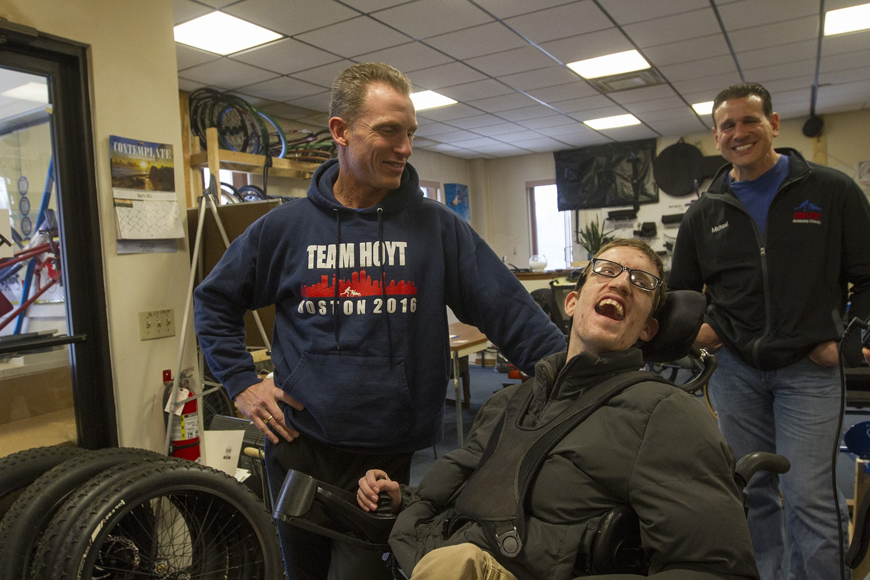 Ted Painter, left, and Nick Draper, will be competing in the 2017 Boston Marathon, using a chair built at Southbridge Tool and Manufacturing. Mike DiDonato, right, helped steer his family's business into making Team Hoyt Running Chairs. (Joe Difazio for WBUR)