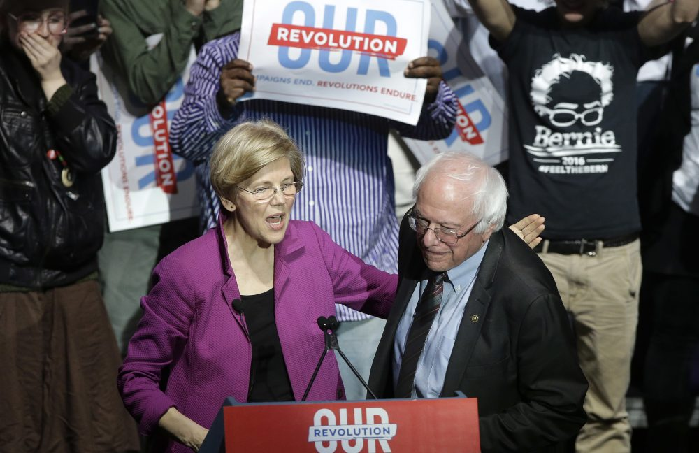 Sens. Elizabeth Warren and Bernie Sanders greet one another on stage at the Friday night rally. (Steven Senne/AP)