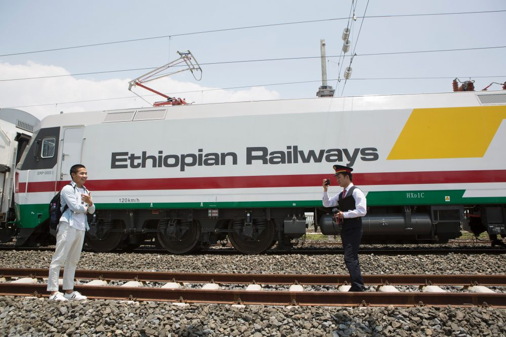 Chinese employees of the new railway linking Addis Ababa, Ethiopia, to Djibouti take pictures in front of the Chinese-made Ethiopian trains in Addis Ababa on Sept. 24, 2016. (Zacharias Abubeker/AFP/Getty Images)