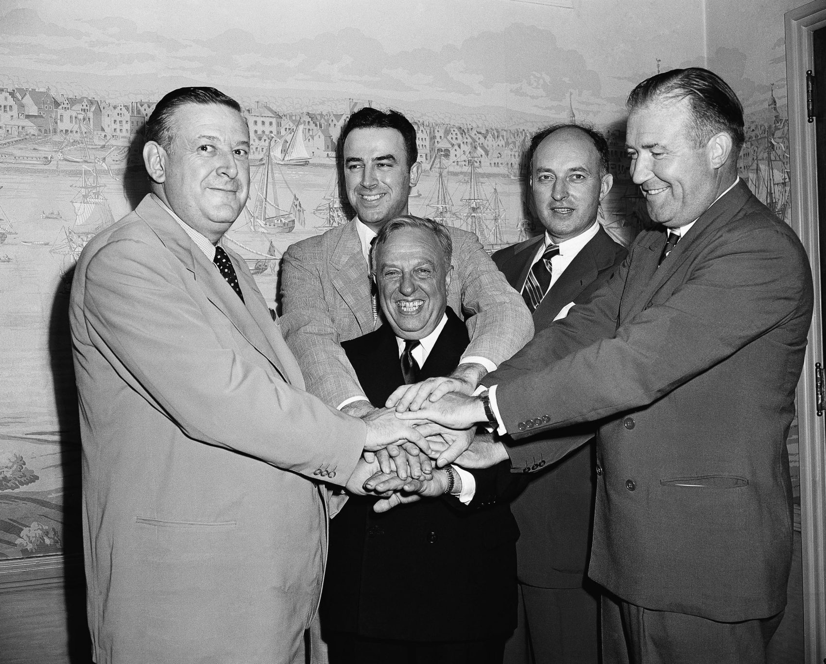 Leo Ferris (second from left) and representatives of the NBL and BAA shake hands after agreeing to a merger in 1949. (John Lent/AP)