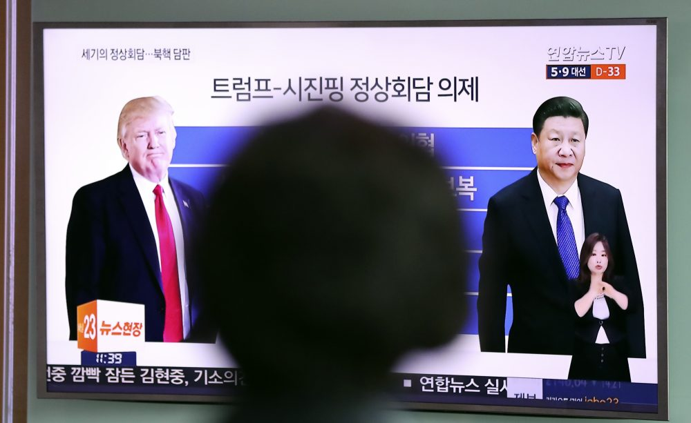 A woman watches a TV news program reporting about the first summit between U.S. President Donald Trump, left, and Chinese President Xi Jinping, at Seoul Train Station in Seoul, South Korea, Thursday, April 6, 2017. (Lee Jin-man/AP)