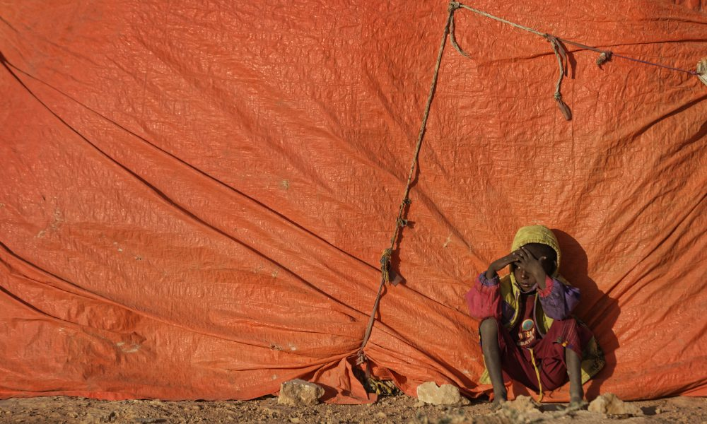 A young Somali boy sits outside his makeshift hut at a camp for people displaced from their homes elsewhere in the country by the drought, shortly after dawn in Qardho, Somalia on, March 9, 2017. (Ben Curtis/AP)