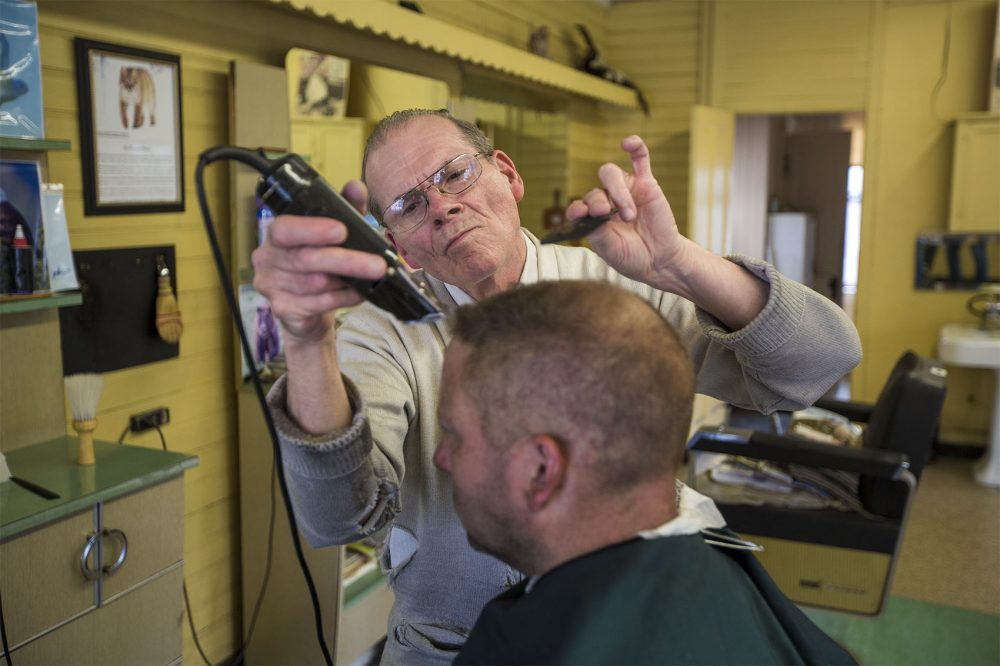 Pete Lareau gives a haircut to Randy Elwell at his barber shop in Townsend, where Lareau has been cutting hair for 56 years. (Jesse Costa/WBUR)