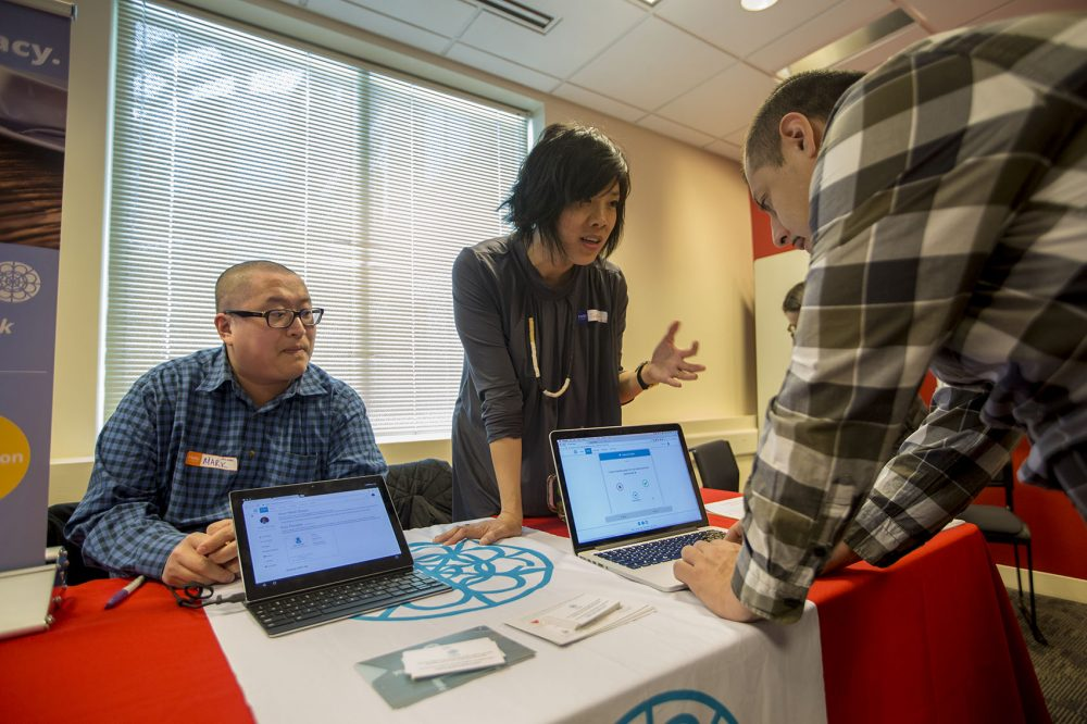 Dr. Mark Zhang and MIT engineer Suelin Chen present their app Cake at the Digital Health Innovation Showcase at Harvard Pilgrim Health Care in Wellesley. (Jesse Costa/WBUR)