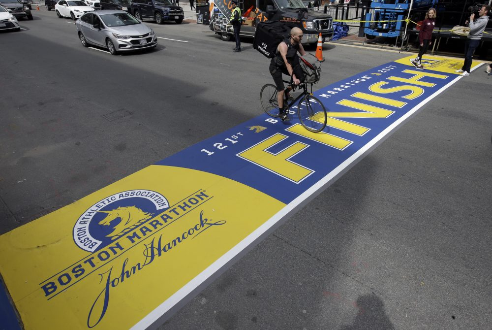A cyclist rides over the newly applied Boston Marathon finish line on Boylston St., Thursday, April 13, 2017, in Boston. (Steven Senne/AP)