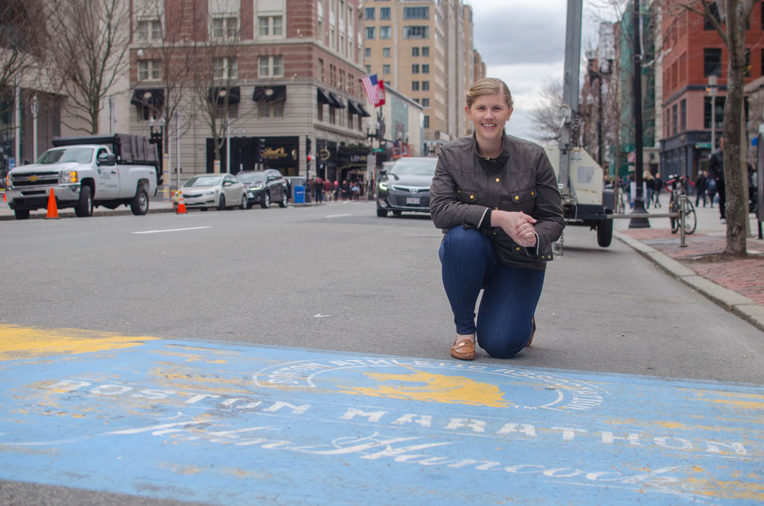 Meghan Connors kneels at the finish line of the Boston Marathon on Boylston Street. This year she's running her fifth Boston Marathon, supporting the MGH Pediatric Oncology division where she was treated for neuroblastoma when she was three years old. (Sharon Brody/WBUR)