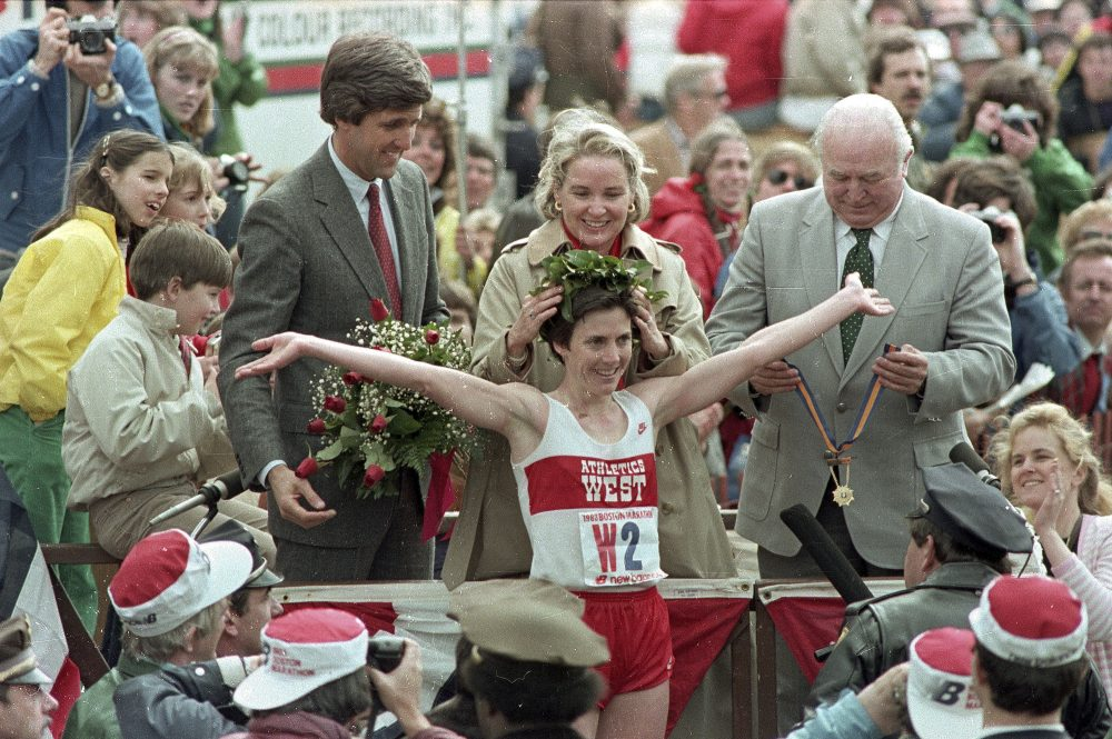 In this April 1983 file photo, Joan Benoit receives her laurel wreath and reacts to cheering crowds after winning the Boston Marathon in record time for the women's division. Lt. Gov. John Kerry, left in red tie, stands behind her. (AP file photo)